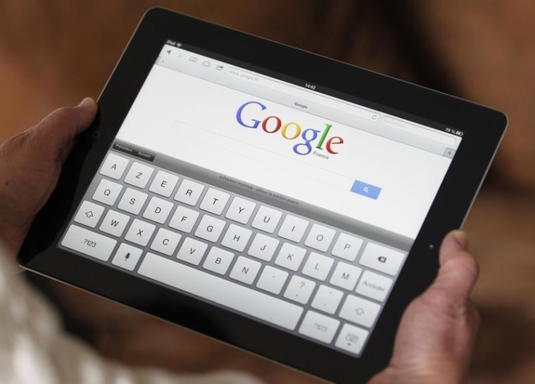 An illustration picture shows a woman holding her Apple Ipad tablet which displays a tactile keyboard under the Google home page in Bordeaux, Southwes...