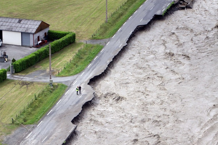 The flooded Lanne River eats away a road in Villelongue, France, June 19, a day after unseasonal storms caused havoc across huge swaths of the country.