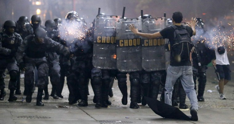 A demonstrator tries to stop the riot police during one of many protests around Brazil's major cities in Rio de Janeiro June 20, 2013.