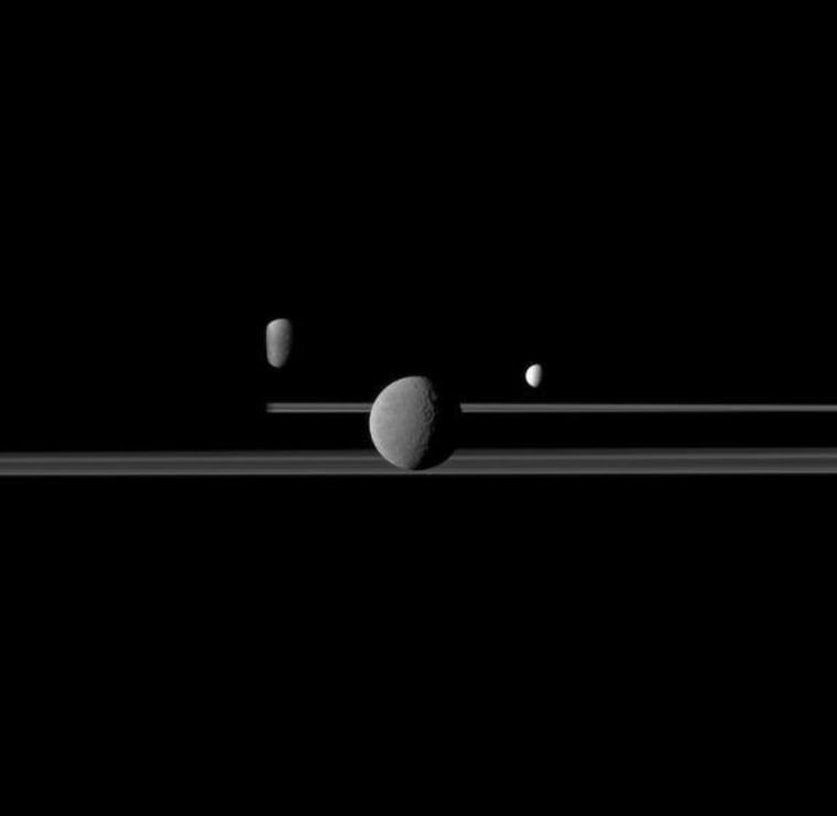 The Cassini spacecraft observes three of Saturn's moons set against the night side of the planet. Saturn is on the left this image but is too dark to see. Rhea (1,528 kilometers, or 949 miles across) is closest to Cassini here and appears largest at the center of the image. Enceladus (504 kilometers, or 313 miles across) is to the right of Rhea. Dione (1,123 kilometers, or 698 miles across) is to the left of Rhea, partly obscured by Saturn.