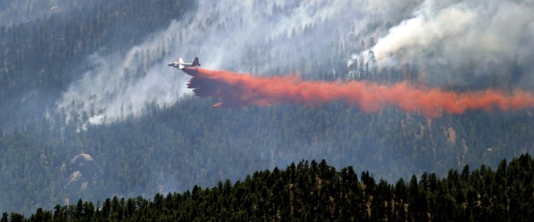 A slurry bomber drops a stream of fire retardant on the Lime Gulch wildfire near Pine, Colo., on Thursday, June 20, 2013. Hot, windy conditions across Colorado left firefighters battling multiple wildfires, while residents in broad swaths of the state were warned about smoke in what has become the state's most damaging fire season in history. (AP Photo/Ed Andrieski)