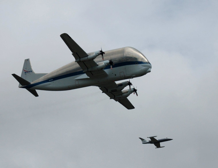 NASA's Super Guppy and a chase plane fly above the mostly cloudy skies of Seattle.