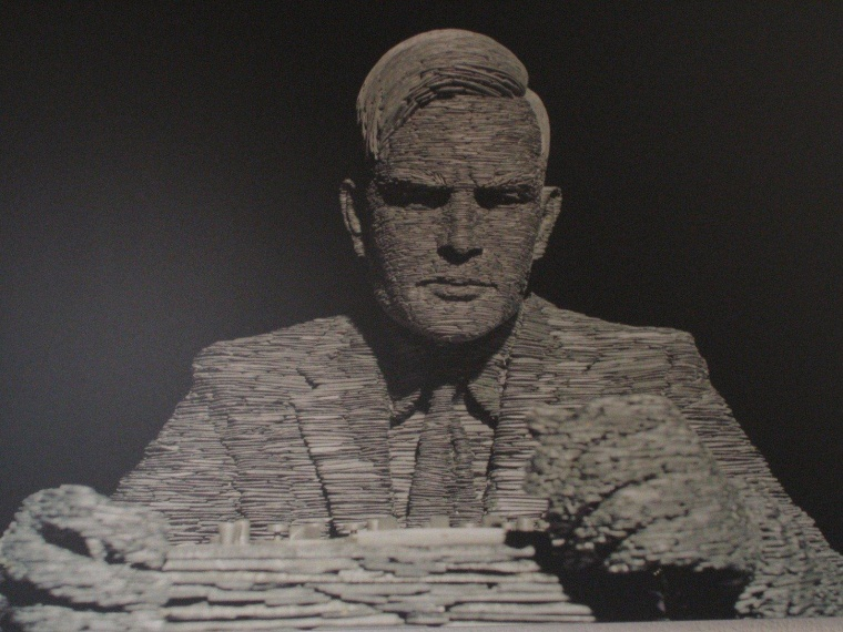 A sculpture that shows computer pioneer Alan Turing looking down at the Enigma Machine was created from stacked slate by British artist Stephen Kettle.