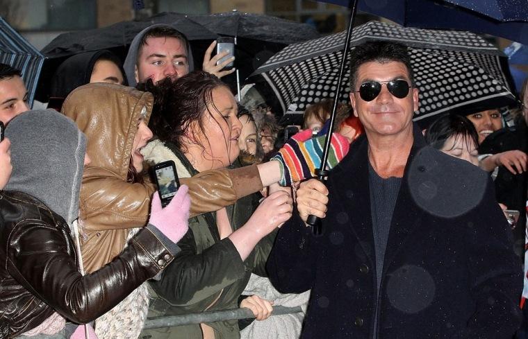 Reality-TV impresario Simon Cowell poses for photos with fans as
