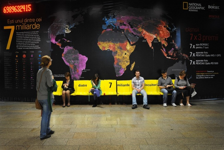 A counter approaches the 7 billion mark at a National Geographic exhibit in a subway station in Bucharest, Romania, highlighting global population density.