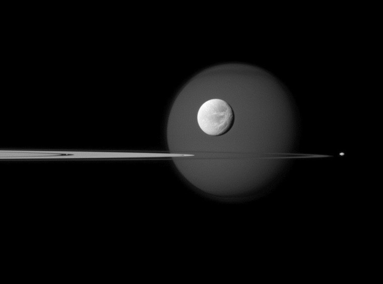 Four moons of Saturn are visible in this image from the Cassini orbiter: Bright Dione is in the foreground, with Titan in the background. The dot just to the right of Saturn's nearly edge-on rings is Pandora, and Pan is just a speck embedded within the rings, to the left of Titan and Dione.