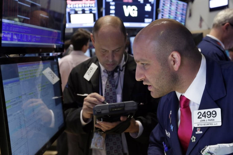 In this Thursday, June 20, 2013, photo, specialist John Parisi, right, works with traders on the floor of the New York Stock Exchange.