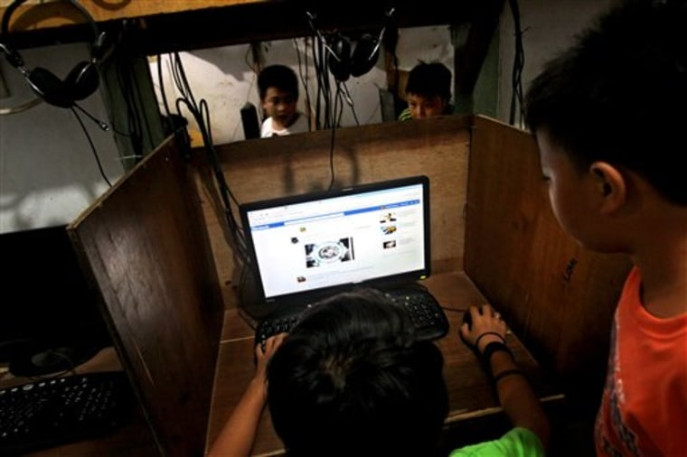 In this June 19, 2013 photo, an Indonesian youth browse his Facebook page at an internet cafe in Jakarta, Indonesia. The use of social networking to g...