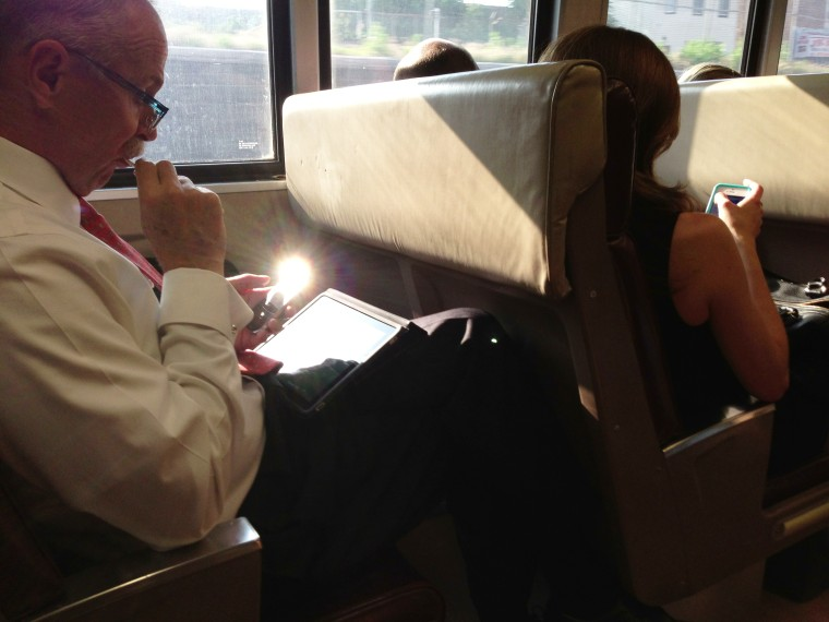 Train commuters use mobile devices