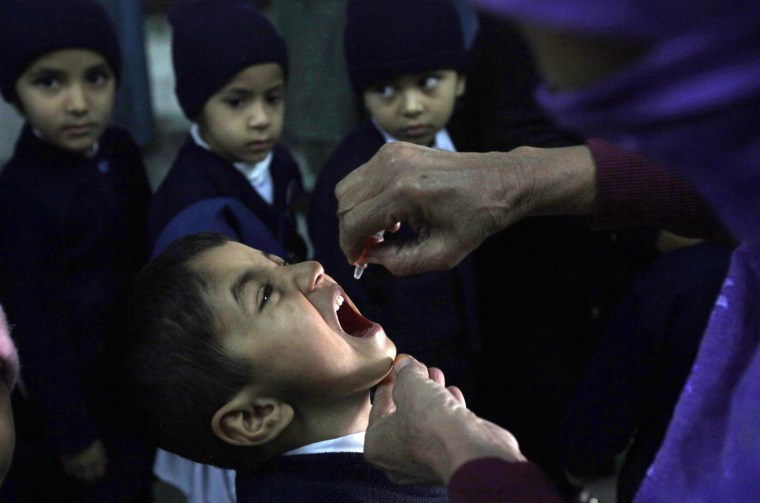 A female polio worker gives polio vaccine drops to a child in Lahore, Pakistan, on Dec. 20, 2012.
