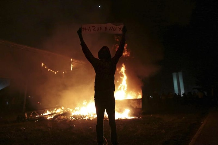 A demonstrator holds a sign next to street structures set on fire during a protest against the Confederations Cup and President Dilma Rousseff's gover...