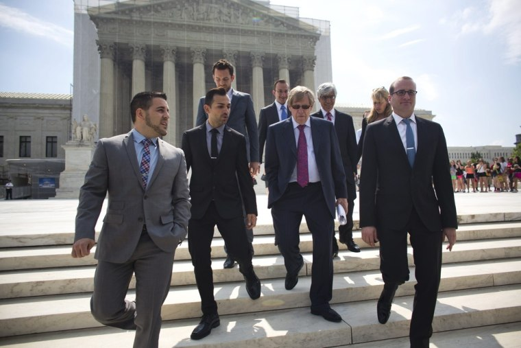 Jeffrey Zarrillo (L) and Paul Katami (C-L), one of the couples seeking to overturn California's Prop 8 ban on same-sex marriage, leave the Supreme Court with one of their attorneys, Ted Olson, after the Supreme Court failed to rule on their case in Washington, D.C. on June 20, 2013.