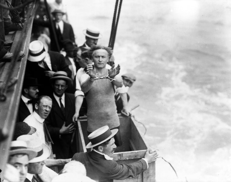 Hungarian-born American magician, escape artist, and psychic debunker Harry Houdini (1874 - 1926) shows his handcuffs as he stands in a wooden box on a boat and prepares to be submerged, a predicament from which he will escape to the delight of onlookers, in the East River in New York City on July 7, 1912.
