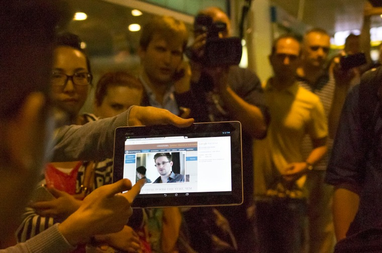 Journalists show passengers arriving from Hong Kong a tablet with a photo of Edward Snowden, a former CIA employee who leaked top-secret documents about sweeping U.S. surveillance programs at Sheremetyevo airport, just outside Moscow, Russia on Sunday.