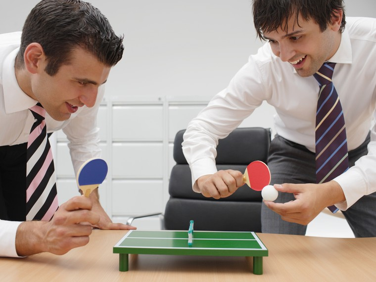 Businessmen playing minature table tennis at desk.