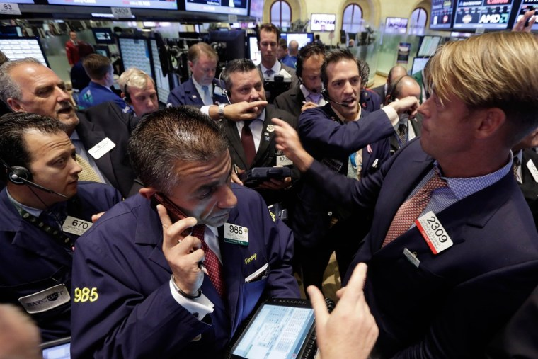Traders gather at the post of specialist Patrick Murphy, right, on the floor of the New York Stock Exchange on Monday. Traders in the U.S. dumped stoc...