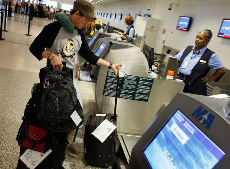 MIAMI - JUNE 12:  A passenger checks in baggage at the United Airlines counter at the Miami International Airport June 12, 2008 in Miami, Florida. Uni...