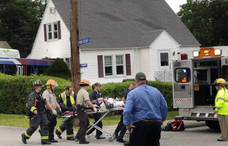 The  driver is wheeled to a waiting ambulance Monday, July 24, after the bus crashed into a house in Aubturn, Mass.