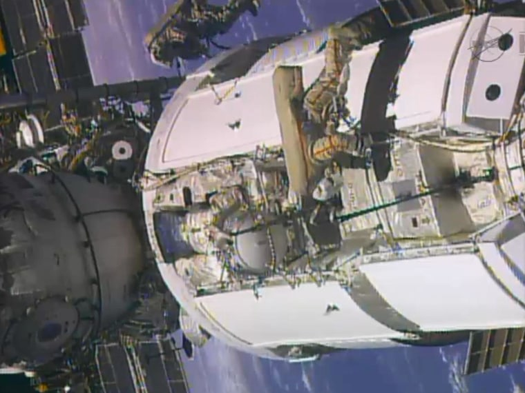 In this frame grab from video provided by NASA, two Russian flight engineers perform maintenance on the International Space Station on Monday.