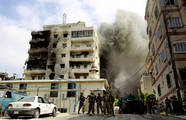 Black smoke rises from the Bilal bin Rabbah Mosque where Sunni cleric Sheik Ahmad al-Assir preaches, while Lebanese troops detonate booby traps, in the southern port city of Sidon, Lebanon, on June 25.