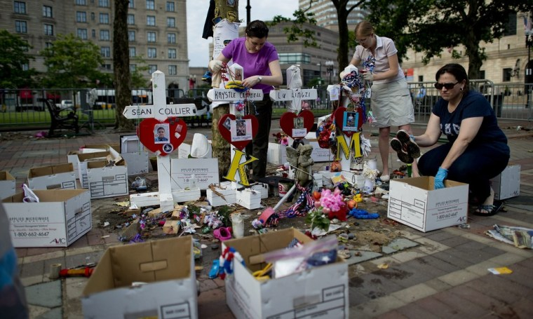 City employees and volunteers remove the remaining items from the Boston Marathon memorial site at Copley Square in Boston on Tuesday.