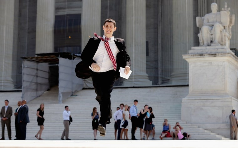 A news assistant runs after a ruling was made outside the U.S. Supreme Court building on June 25, in Washington, D.C. The court ruled that Section 4 of the Voting Rights Act is unconstitutional.