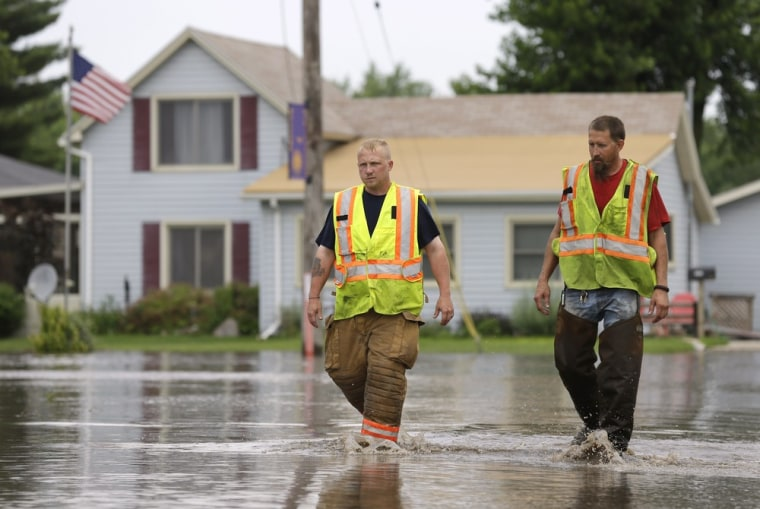 New Hartford firefighters Clint Olmstead, left, and Jon LeBahn walk through floodwaters on Tuesday in New Hartford, Iowa. Hundreds of residents obeyed an order to evacuate their homes in this northeast Iowa town before floodwaters from a rising creek could strand them.