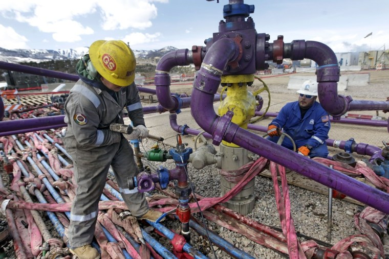 In this March 29, 2013 photo, workers tend to a well head during a hydraulic fracturing operation at an Encana Oil & Gas (USA) Inc. gas well outside R...
