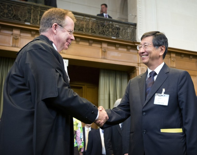 Attorney General of Australia Mark Dreyfus, left, shakes hands with Japanese Deputy Minister of Foreign Affairs Koji Tsuruoka at the International Court of Justice in The Hague, Netherlands, Wednesday.
