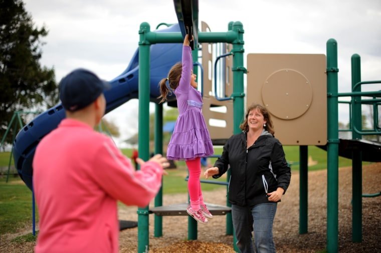 Charlie and Karen Morgan play with their daughter, Casey, on the playground in Rye, N.H., in May 2012.