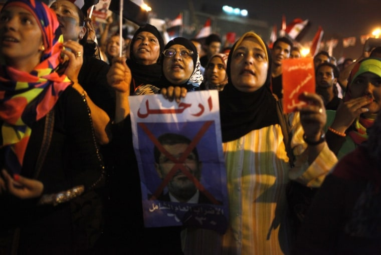 A protester holds a crossed out picture of the president while chanting anti-Morsi and anti-Muslim Brotherhood slogans as they wait in Tahrir Square ahead of President Mohammed Morsi's public address, in Cairo June 26, 2013.