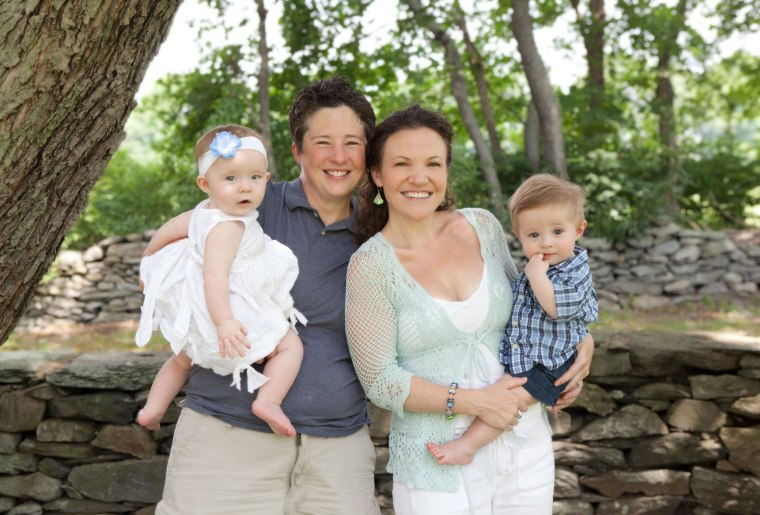 Army Maj. Shannon McLaughlin and her wife, Casey, hold their twins, Grace and Grant