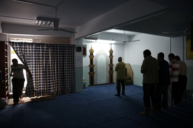 A man enters a makeshift mosque where others Muslim faithful pray at Kallithea suburb in Athens on May 22, 2013.