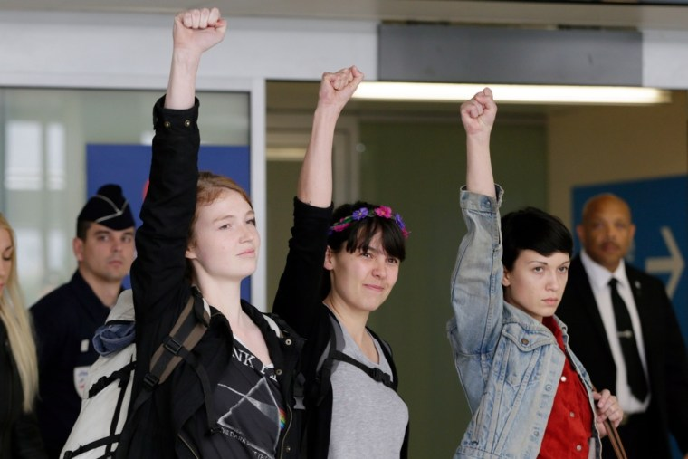 Members of the radical protest group Femen, (from left) Josephine Markmann, Pauline Hillier and Marguerite Stern raise their fists upon arrival at Orly airport on Thursday in Paris.