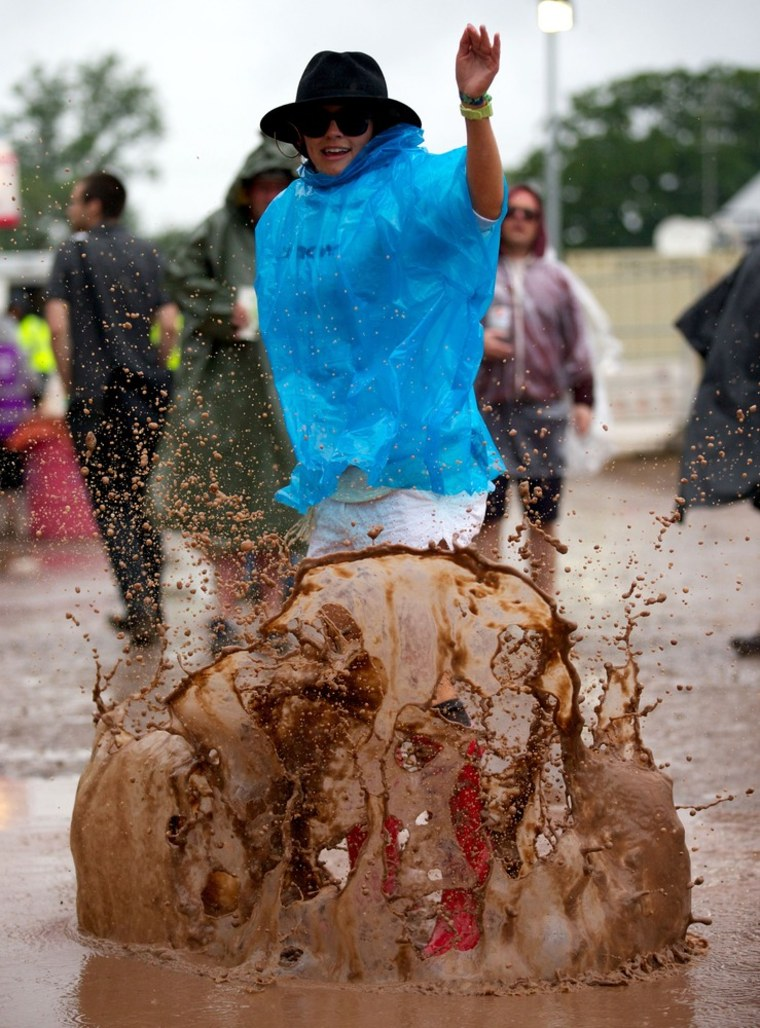 A festival goer jumps in a mud puddle on the second day of the Glastonbury Festival.