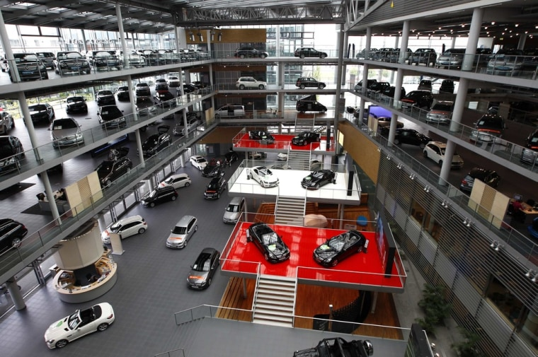 Mercedes-Benz cars are displayed in a dealership of German car manufacturer Daimler in Munich May 17, 2013. How many Mercedes staff does it take to se...