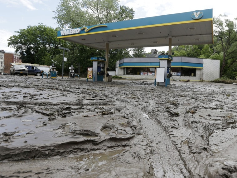Mud fills the parking lot of a convenience store after flooding on Friday, June 28, 2013, in Fort Plain, N.Y. Severe flooding caused by the spring and early summer's persistent rains damaged houses, closed roads and forced people to flee their homes Friday in New York's Mohawk Valley. Heavy rains Thursday and into early Friday caused the Mohawk River to overflow it banks where it traverses the southern end of Herkimer County, located 60 miles east of Syracuse.