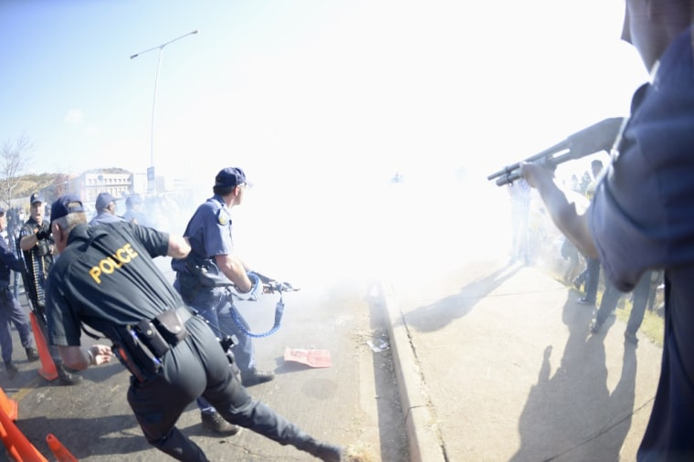 Smoke fills the air as police use stun grenades in an attempt to disperse protesters outside the University of Johannesburg in Soweto, ahead of a visit by U.S. President Barack Obama, June 29, 2013.