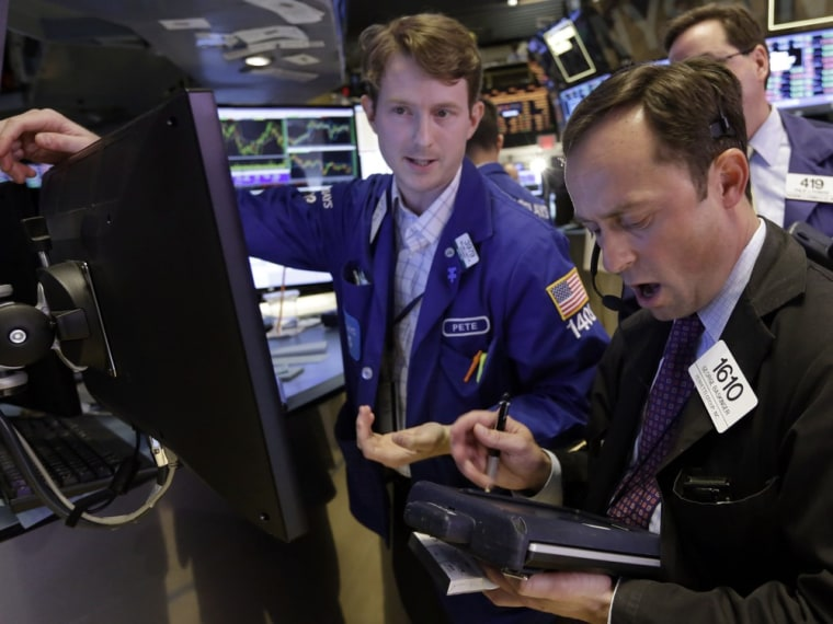 Specialist Peter Elkins, left, and trader George Baskinger work on the floor of the New York Stock Exchange on Friday, June 28, 2013. Stocks ended mos...