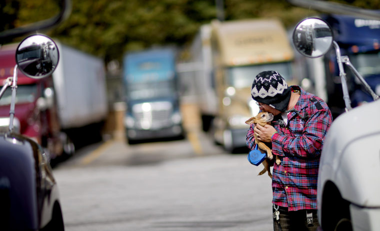 Truck driver Jimmy Mayes holds his chihuahua, Coco, while waiting to pick up a load at a truck stop Tuesday, Oct. 30, 2012, in Atlanta. Even amid a st...