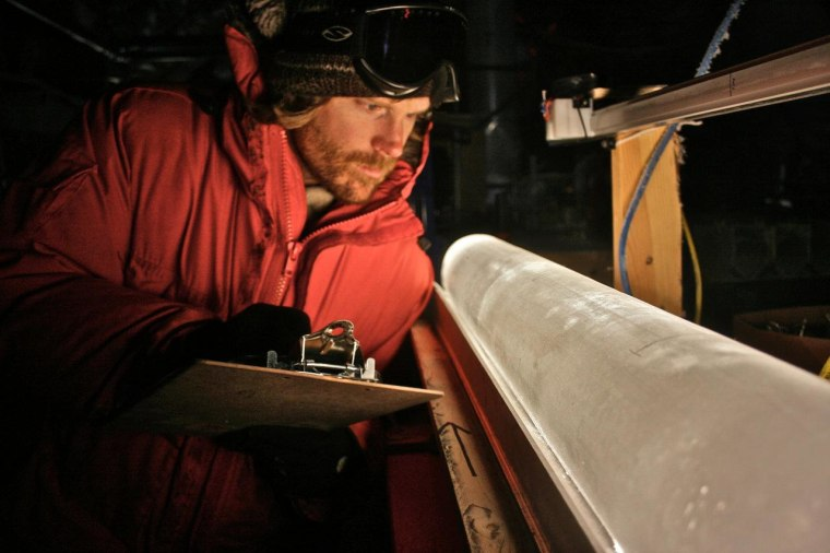 Scientist Brian Bencivengo of the National Ice Core Laboratory examines an ice core from the West Antarctic Ice Sheet. Samples from these cores provide information about past air temperatures at the location from which the core was obtained.