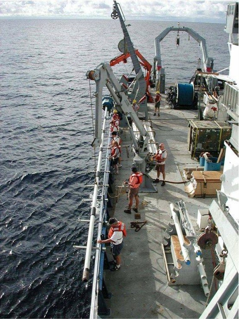 Researchers prepare to deploy a core barrel off the side of the Reseach Vessel Melville to collect sediments from the ocean floor. Samples from these cores provide information about past sea surface temperatures at the location from which the core was obtained.