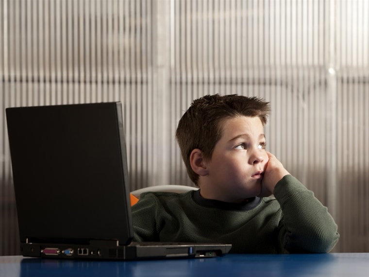 A boy works on a laptop.