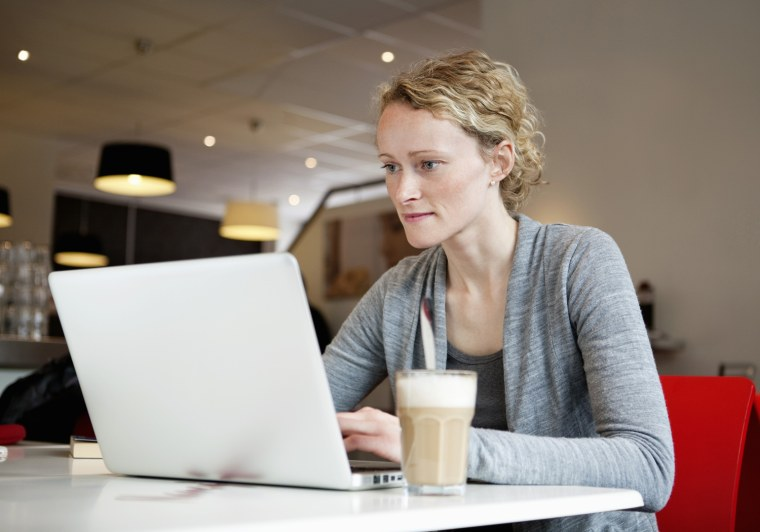 Woman with laptop and coffee at coffeehouse