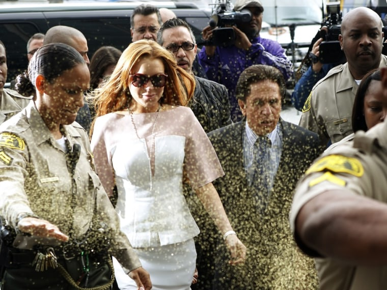 Actress Lindsay Lohan is showered with gold glitter as she arrives with her attorney Mark Heller at Los Angeles Superior Court on Monday.