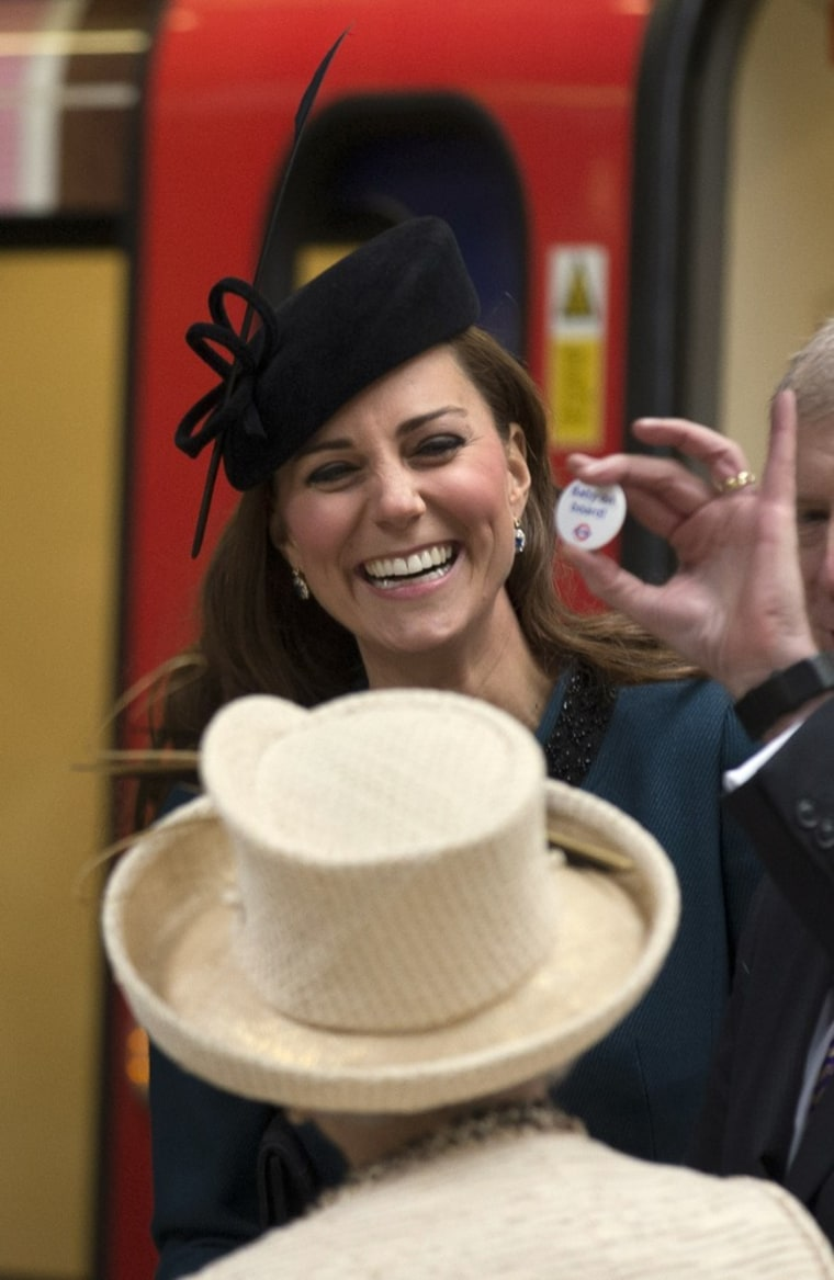"""Duchess Kate accepts a badge that reads """"Baby on Board,"""" normally available to pregnant passengers to encourage others to give them a seat on the Lond..."""