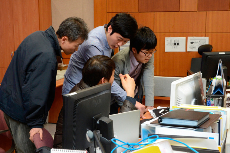 Employees of the Korean Broadcasting System (KBS) check computers as they try to recover a server of the company's network at main office of KBS in Seoul, on March 21.