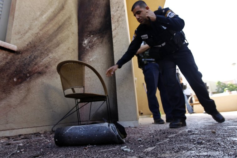 Israeli police officers stand near the remains of a rocket fired by Palestinian militants after it landed in the town of Sderot on Thursday.