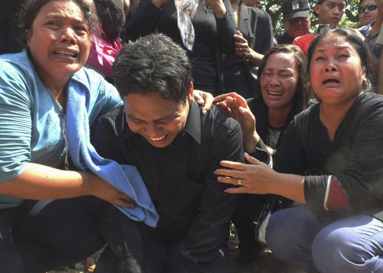 Members of the congregation of Batak Christian Protestant Church (HKBP) cry as an excavator demolishes their church in Bekasi, on the outskirts of Jakarta, Indonesia on March 21, 2013.