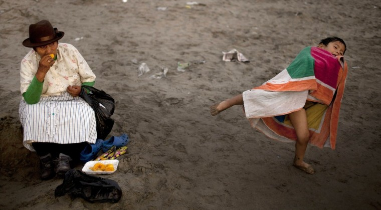 A woman snacks on mango fruit as her grandson plays nearby on Agua Dulce beach in Lima, Peru.